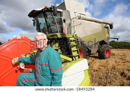 Farmer standing by harvester - stock photo