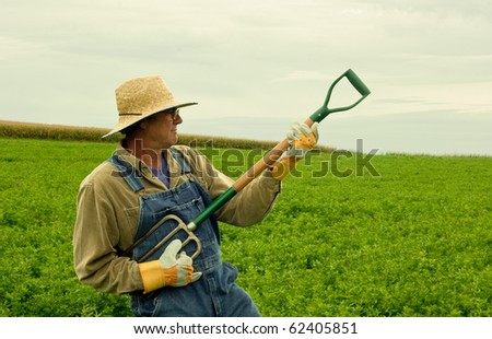 farmer standing in a hay field playing air guitar on his fork - stock photo