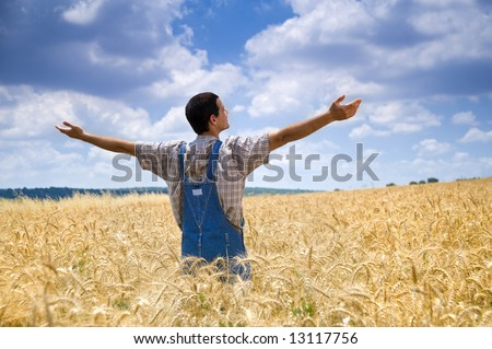 farmer standing in a wheat field with his arms spread out - stock photo