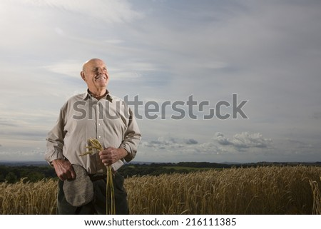 Farmer standing in wheat field - stock photo
