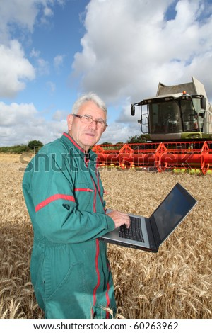 Farmer standing in wheat field with computer - stock photo