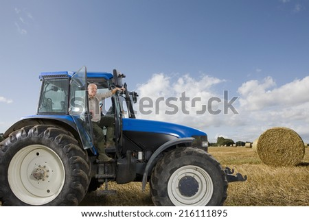 Farmer stepping down from tractor in hay field - stock photo