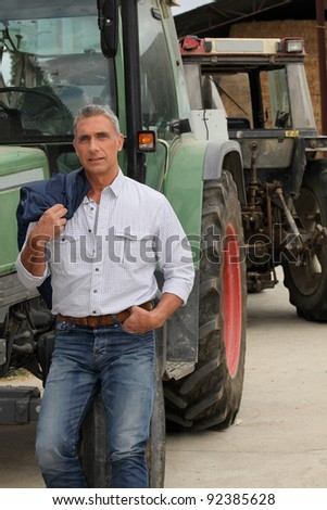Farmer stood by tractor - stock photo