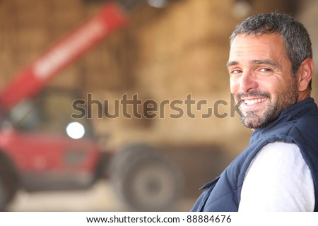 Farmer stood in front of bails of hay - stock photo