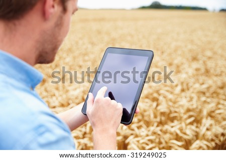 Farmer Using Digital Tablet In Field Of Wheat - stock photo
