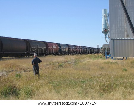 farmer watching as train pulls out with seasons crops from saskatchewan - stock photo