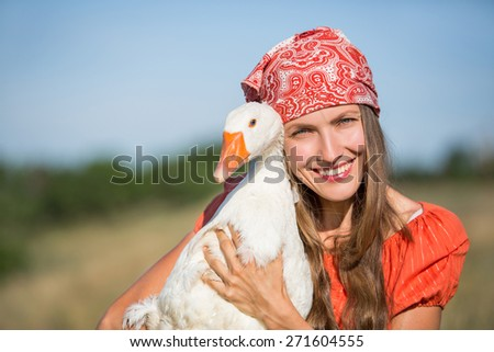 Farmer with a goose over green natural background, focus on woman - stock photo