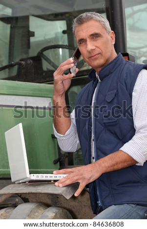 Farmer with a laptop and cellphone - stock photo
