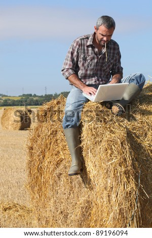 Farmer with a laptop on a haystack - stock photo