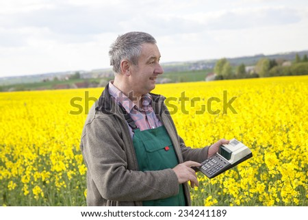 Farmer with calculation engine in the rape field - stock photo