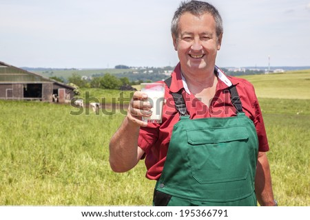 Farmer with glass of milk before his court - stock photo