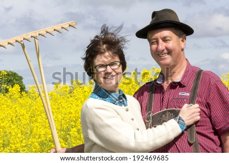 Farmer with his wife before the rape field - stock photo