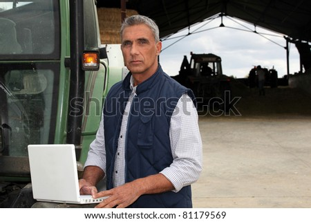 Farmer with laptop stood by tractor - stock photo