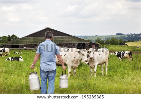 Farmer with milk churns in front of his cows - stock photo