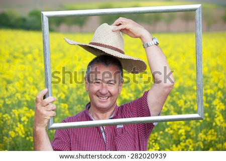 Farmer with photo frame is placed in canola field - stock photo