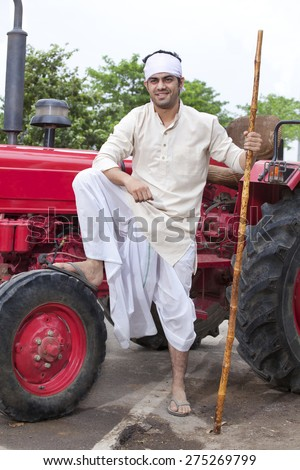 Farmer with stick and leg on tractor wheel - stock photo