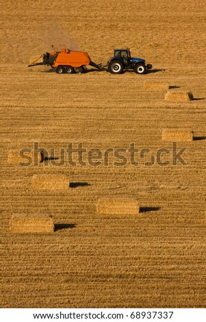 farmer with tractor and bales - stock photo