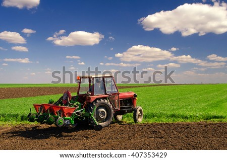 Farmer with tractor sowing on agricultural fields on sunny spring day.