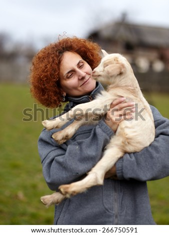 Farmer woman holding a cute baby goat outdoor - stock photo