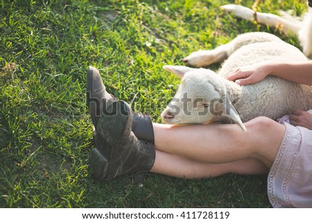 Farmer woman resting outdoor with farm animal. Cute young lamb at her legs. Woman legs in old leather boots. - stock photo