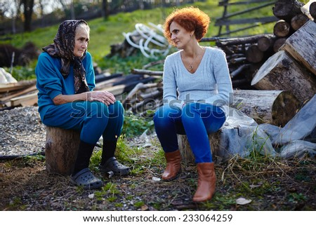 Farmer women, mother and daughter sitting on logs outdoor and chatting - stock photo