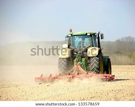 Farmer working with tractor in agricultural field - stock photo
