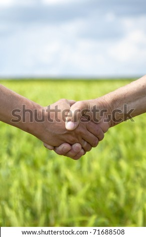 Farmers handshake in green wheat field. - stock photo
