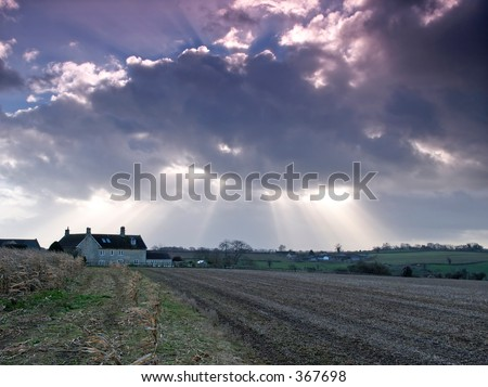 Farmhouse in a harvested field with the sun breaking through above - stock photo