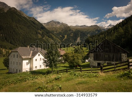 Farmhouses with Fence and Mountains in the Background in Summer, Mallnitz, High Tauern, Alps, Austria, Europe - stock photo