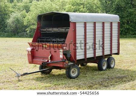 farming chopper wagon on a fresh cut hay field - stock photo