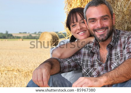 Farming couple sat by hay - stock photo