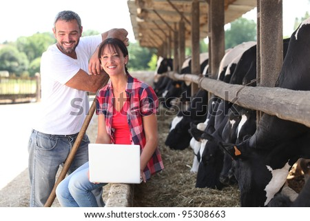 Farming couple stood by cows - stock photo