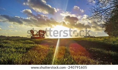 Farming equipment on a field with a sunset behind - stock photo