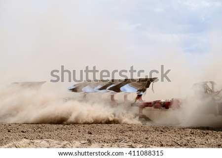 Farming machinery, plow running in the field, fertile land, the agricultural industry, the steel frame, plow powerful close-up, equipment for cultivation - stock photo