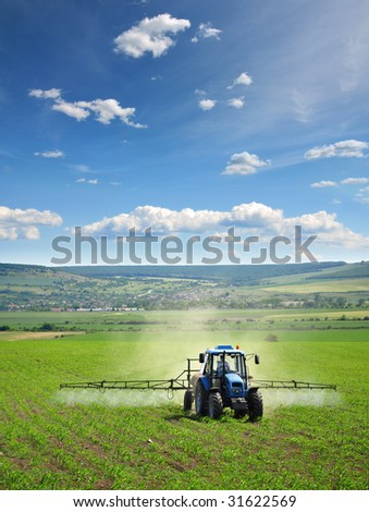 Farming tractor plowing and spraying on field vertical - stock photo