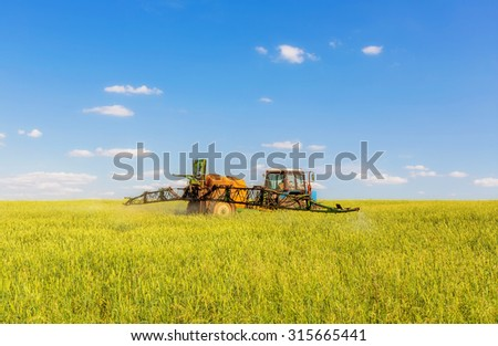 Farming tractor spraying green field beneath blue sky with white clouds - stock photo