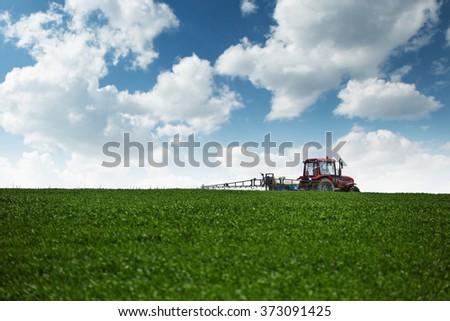 Farming tractor spraying green wheat field with sprayer