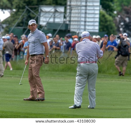 FARMINGDALE, NY - JUNE 17: Phil Mickelson and his instructor, Butch Harmon, review issues with his last swing during the 2009 US Open on June 17, 2009 in Farmingdale, NY. - stock photo