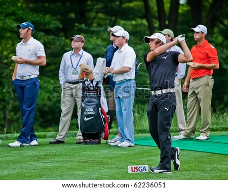 FARMINGDALE, NY - JUNE 16: Rickie Fowler tees off the 14th hole during the 2009 US Open on June 16, 2009 in Farmingdale, NY. Dustin Johnson (left) and Justin Leonard look on. - stock photo