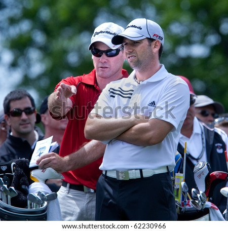 FARMINGDALE, NY - JUNE 17: Sergio Garcia and his caddy discuss the tee shot off the sixth hole at the Black course during the 2009 US Open on June 17, 2009 in Farmingdale, NY. - stock photo