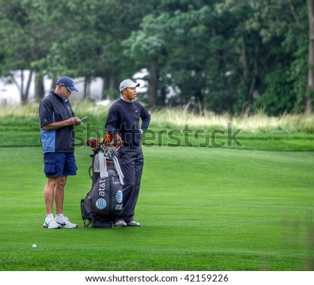 FARMINGDALE, , NY - JUNE 16: Tiger Woods and his caddy contemplate the next shot at the 12th hole on the Black Course during the 2009 US Open on June 16, 2009 in Farmingdale, NY. - stock photo