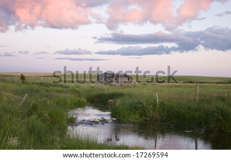 Farmland and buildings in the foothills of the rocky mountains in southern Alberta, Canada - stock photo