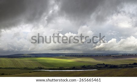 Farmland and lake during bad weather - stock photo