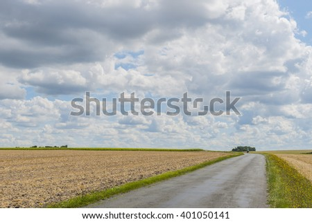 Farmland field with cyclist near Royan France with great clouds and rain clouds.