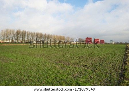 Farmland near a city in winter - stock photo