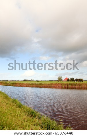 Farmland with canal under cloudy sky, the Netherlands - stock photo