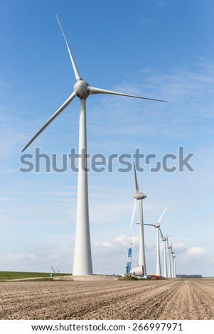 Farmland with construction work at a windfarm along the dike of the Noordoostpolder in the Netherlands. The axle height is 135 meter and the wings have a peak  height of almost 200 meter. - stock photo