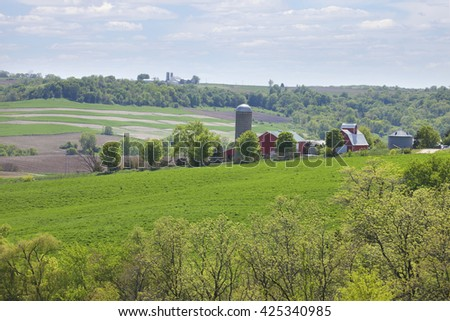 Farms on a hillside in the Iowa countryside during spring - stock photo