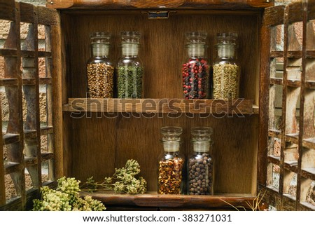 Farms vintage Spice Rack or Storage Cabinet: Wall Mount - Display Shelf, Two Drawers, Six Glass Bottles with oregano on rural background village life - stock photo