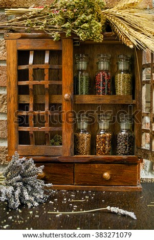 Farms vintage Spice Rack or Storage Cabinet: Wall Mount - Display Shelf, Two Drawers, Six Glass Bottles with lavender, whole wheat and oregano on rural background village life - stock photo